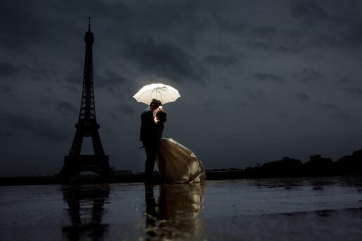 evening shot of a couple kissing in the rain in paris with the eiffel tower in the background
