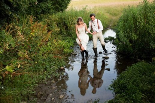 married couple passing the stream in wellington boots