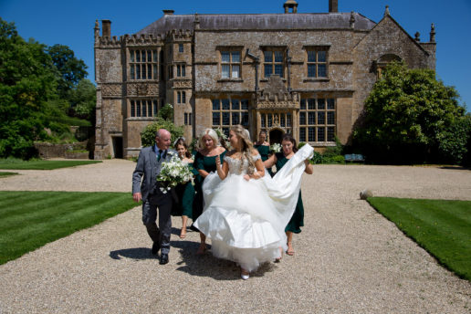 bride and bridesmaids walking in front of brympton house
