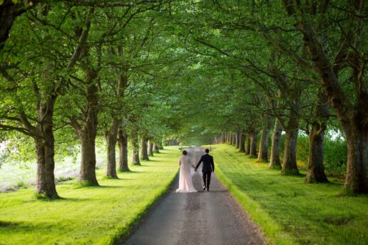 bride and groom walking down the long driveway leading to btympton house