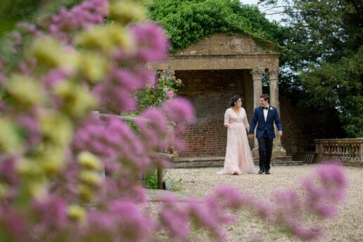 bride and groom walking by the temple at brympton d'evercy