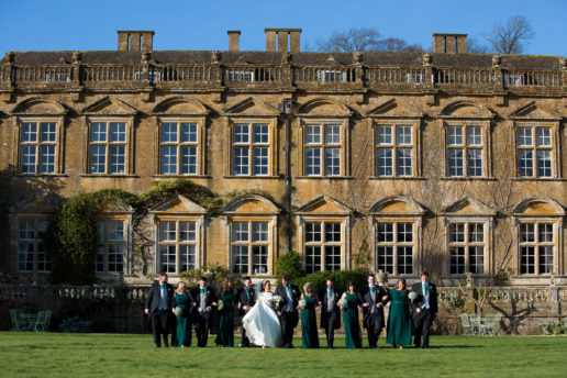 bridal party walking on the lawn with the brympton house in the background