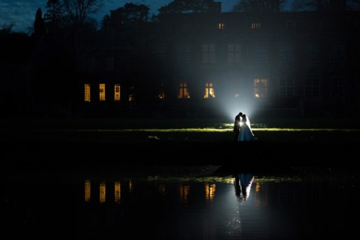 reflection of bride and groom in brympton house lake