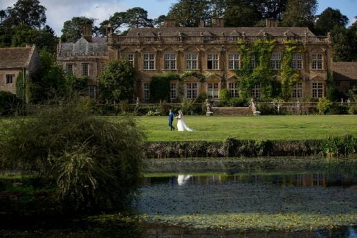bride and groom walking by the lake with brymton house in the background