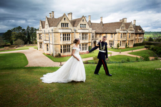 wedding couple walking in front of coombe lodge in somerset