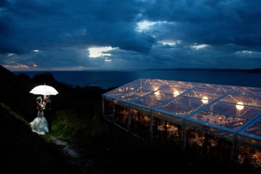 twilight shot of wedding couple with a white umbrella with Italian sea behind them