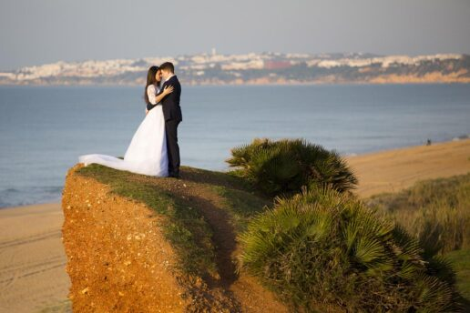 wedding couple on the top of the orange cliff at falesia beach on the algarve coast in portugal