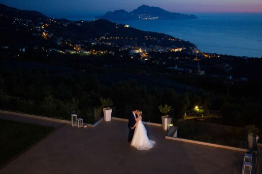 twilight shot of bride and groom at villa eliana in sorrento with capri island in the background