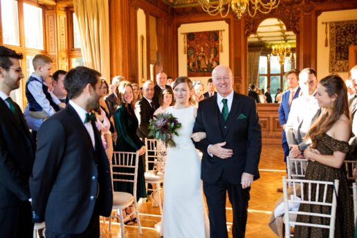 bride walking with her dad towards the groom in maximillian room at manor by the lake