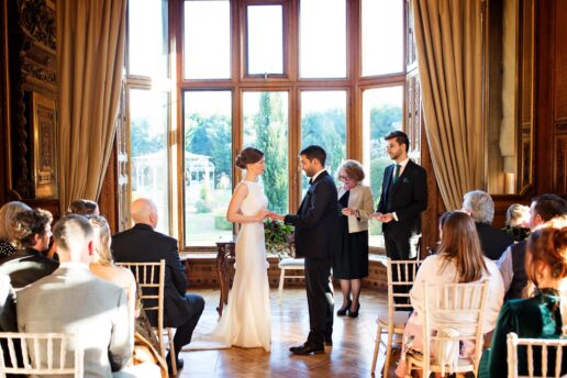 bride and groom exchanging rings during wedding ceremony in maximillian room at manor by the lake