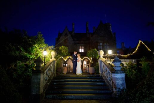 wedding couple in front of manor by the lake at night