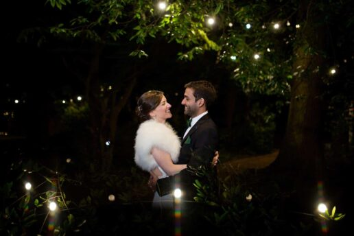 bride and groom walking by the lake with fairylight above them at manor by the lake