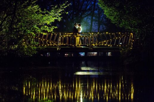 wedding couple on the bridge at night at manor by the lake