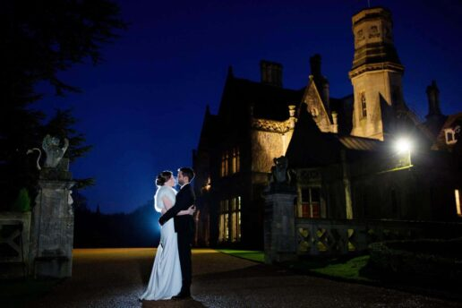 night shot of the couple in front of the manor by the lake in cheltenham