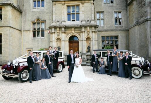 bridal party with wedding cars at the entrance of orcahrdleigh