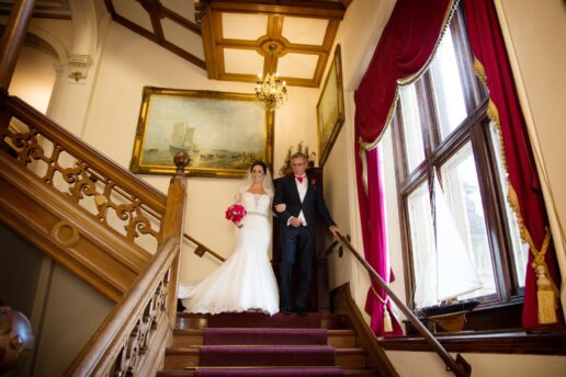 bride walking down the stairs with her father at orchardleigh house