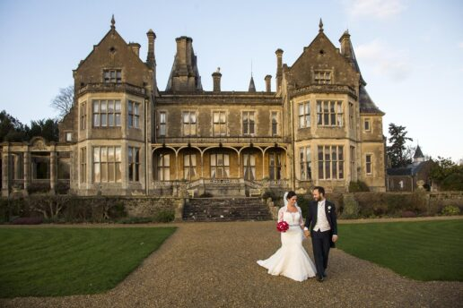 bride and groom walking if front of orchardleigh house