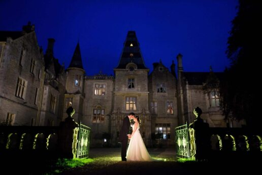 evening shot of wedding couple in front of the entrance to orchardleigh house