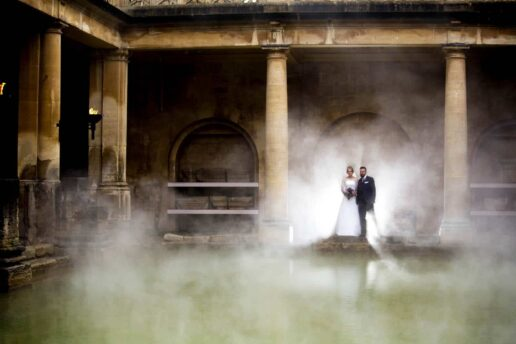 wedding couple at the sunrise ceremony at the roman baths with hot steam behind them