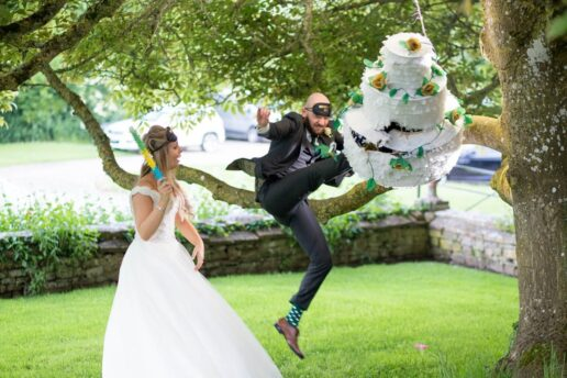 groom kicking pinata cake in front of elmore court