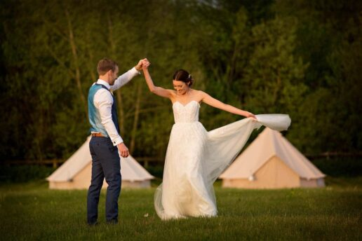 bride and groom dancing with bell tents in the background at elmore court