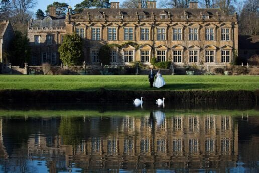 bride and groom in front of the brympton house lake