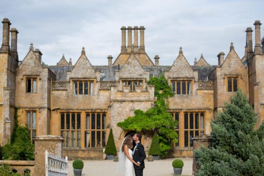 bride and groom kissing in front of dillington house in somerset