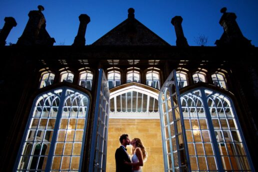 night shot of bride and groom kissing in front of the orangery at dillington house in somerset