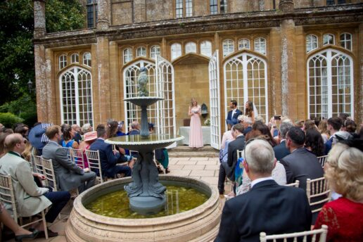 bridesmaid doing the reading during an outdoor wedding ceremony in front of the orangery at dillington house