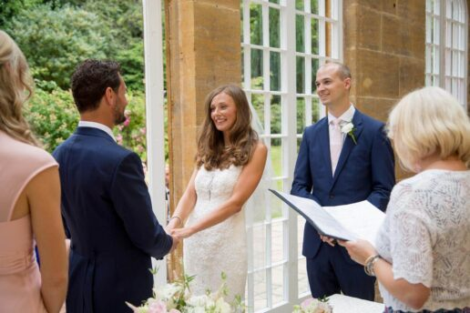 wedding couple exchanging vowels inside the orangery at dillington house