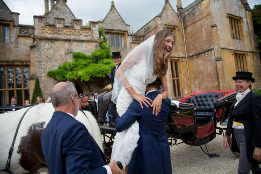 groom is picking up the bride to put her to horse and carriage in front of dillington house in somerset