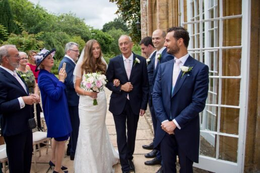 bride and father walking towards outdoor ceremony at dillington house in somerset