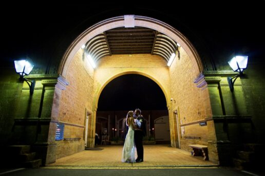 night shot of the kissing couple at the entrance to the mews building at dillington estate