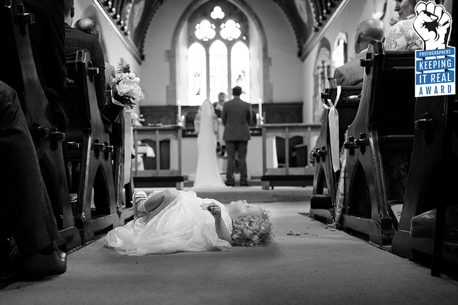 flower girl laying down in the church aisle during wedding ceremony