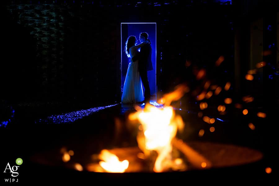 bride and groom lit up by blue light with a fireplace in front of them at upcote barn in cotswolds