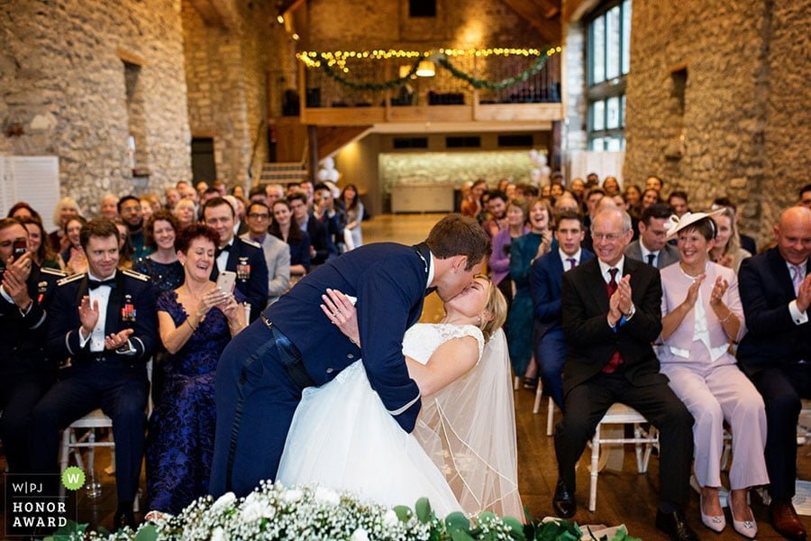 groom kissing at the end of wedding ceremony at priston mill in somerset