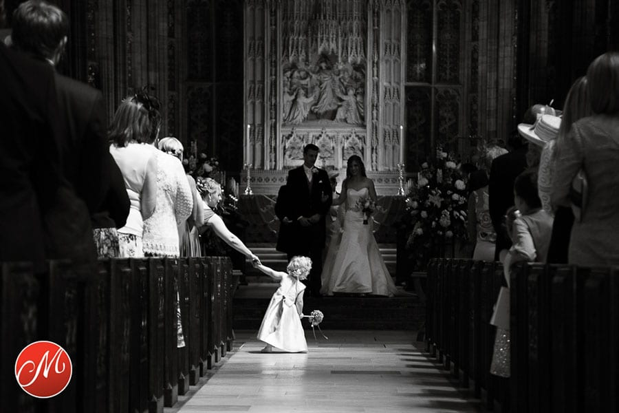 flower girl stepping out to the aisle to see the bride and groom at sherborne abbey in dorset