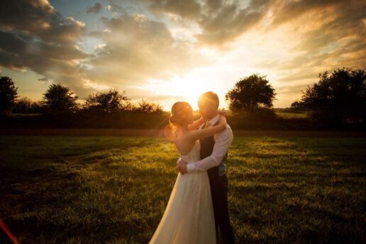 bride and groom embracing and looking at each other with a sun behind them in the field at Caerhays Estate