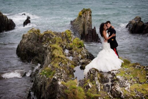 bride and groom hugging each other on the sea rock with a sea behind them at polhawn fort beach in cornwall