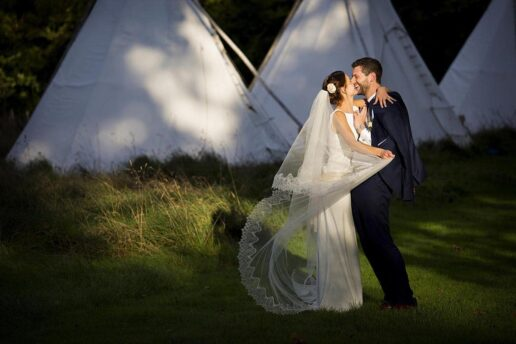 bride and groom kissing each other in the evening sun with a tipis behind them at Cornish Tipi Weddings
