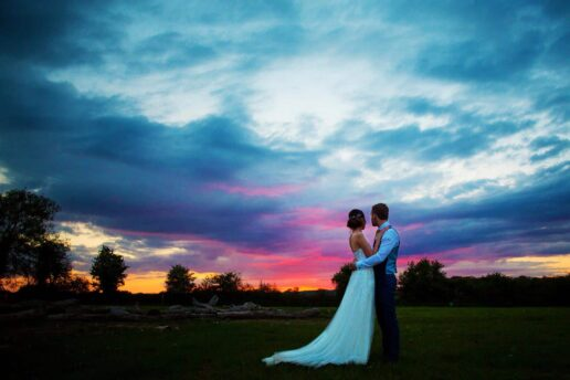 wedding couple looking at dramatic sky after the sunset in the field at Bonconnoc House in Cornwall