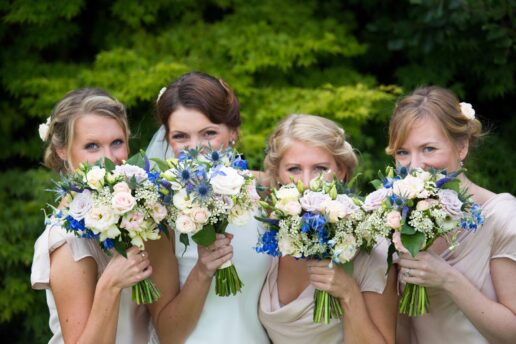bridesmaids holding their flower bouquets in front of their faces at Trebah garden in cornwall