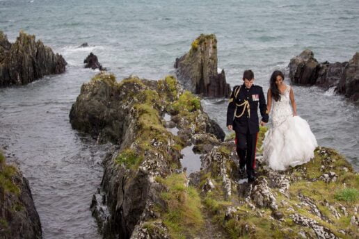 wedding couple holding hands and walking on the rocks with sea behind them at polhawn fort
