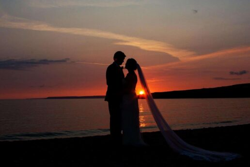silhouette of wedding couple during sunset at Chiddlecombe in devon
