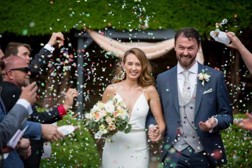 guests throwing confetti on wedding couple after their outdoor ceremony at Bovey castle in dartmoor