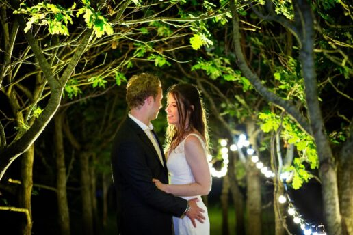backlit portrait of wedding couple at night with trees and fairy light behind them at the Anran wedding venue in Devon