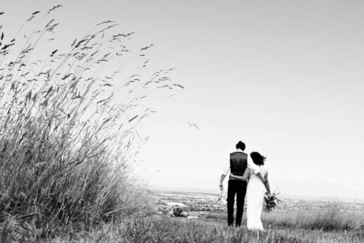 wedding couple walking away on the field path at Eggbeer Farm in devon
