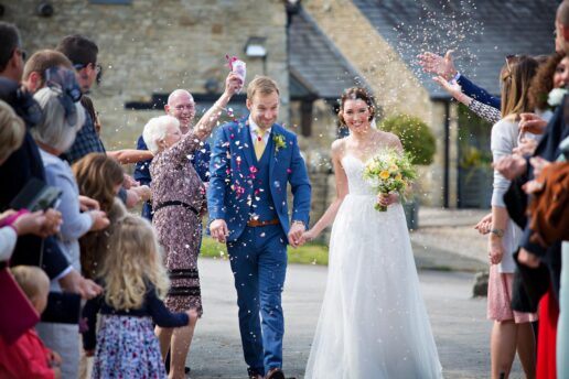 guests throwing confetti at bride and groom at ash barton estate