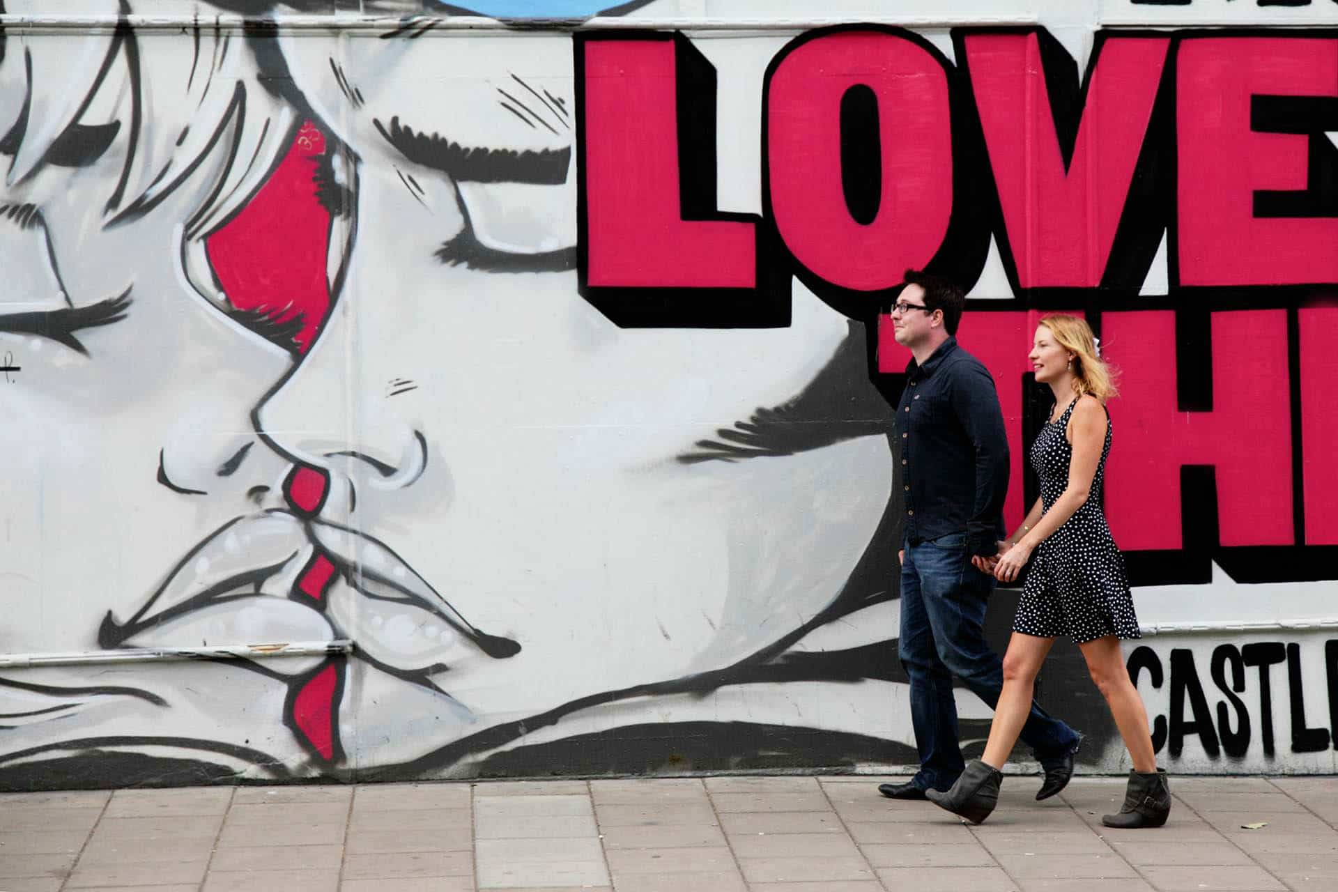 couple walking holding hands in front of big graffiti with love written