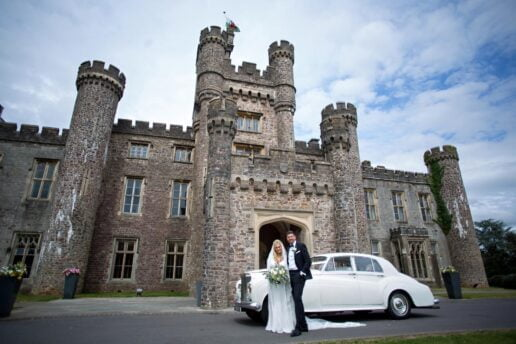 bride and groom with white wedding car in front on hensol castle